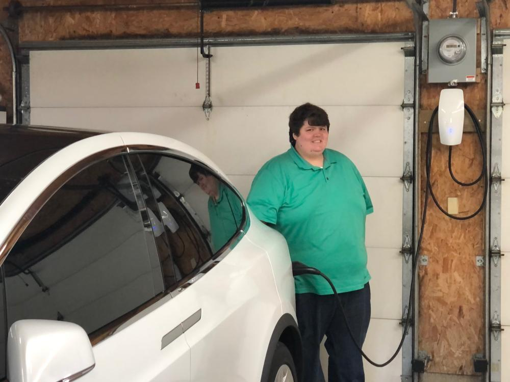 Member Craig Hart with his Tesla X electric vehicle and charging station Midwest Electric helped install